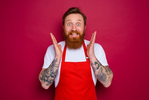 Gelukkige geïsoleerde chef-kok met baard en rode schort