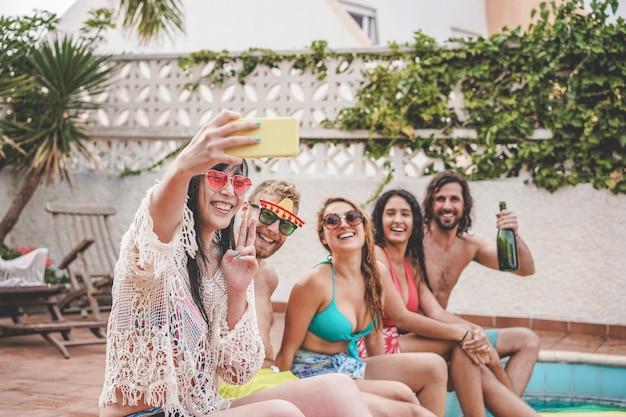 Gelukkige gekke vrienden die plezier hebben met het nemen van selfie en naast het zwembad zitten -