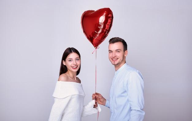 Gelukkige geliefden met een rode hartvormige ballon.