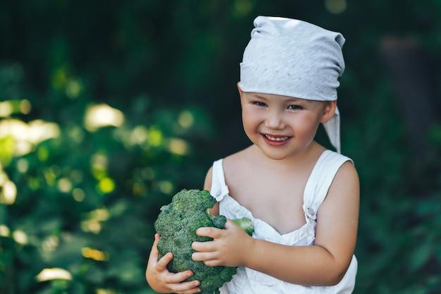 Gelukkige gelukkige glimlachende de landbouwersjongen van litle in witte overall en grijze haarband die verse organische broccoli in handen houden