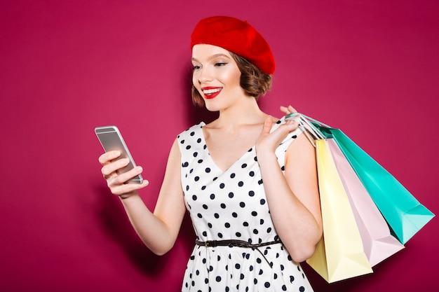 Gelukkige gembervrouw in kleding met pakketten die smartphone over roze gebruiken