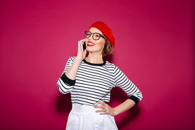 Gelukkige gembervrouw in oogglazen met wapen op heup die door smartphone spreken en weg over roze kijken