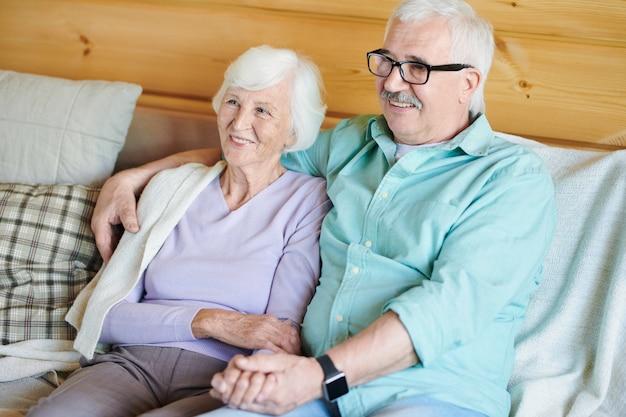 Gelukkige gepensioneerde paar in vrijetijdskleding zittend op de bank voor tv en kijken naar film of programma thuis