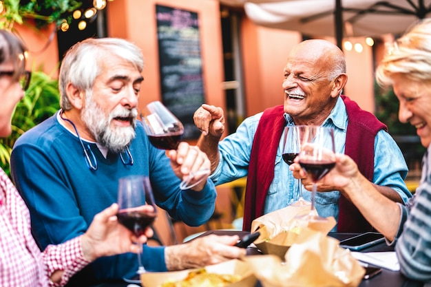 Gelukkige gepensioneerde vrienden die plezier hebben met het drinken van rode wijn op een pre dinner party
