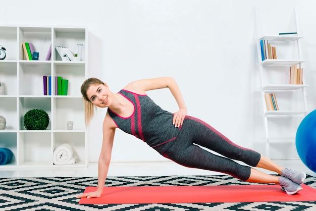 Gelukkige geschiktheids jonge vrouw die sportkleding draagt die oefening in de woonkamer doet