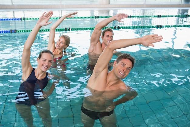 Gelukkige geschiktheidsklasse die aquaaerobics in zwembad doen bij het vrije tijdscentrum