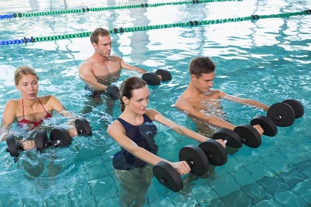 Gelukkige geschiktheidsklasse die aquaaerobics met schuimdomoren doen in zwembad op het vrije tijdscentrum