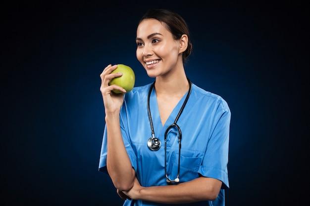 Gelukkige gezonde arts die groene appel geïsoleerd houdt