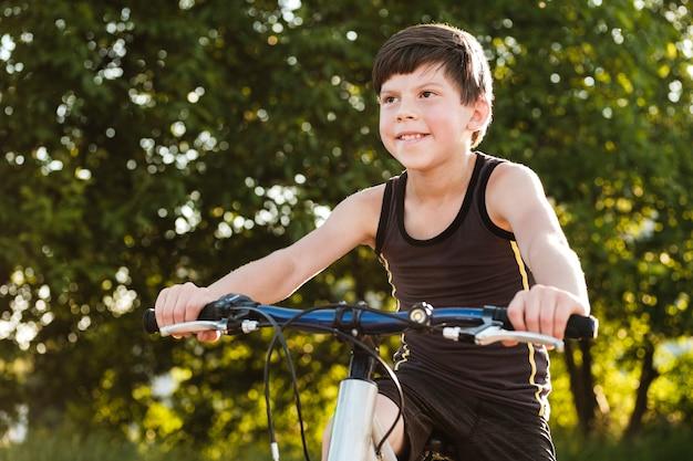 Gelukkige gezonde jonge jongen die zijn fiets berijdt