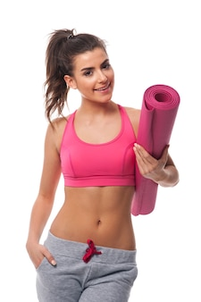 Gelukkige gezonde vrouw met yogamat
