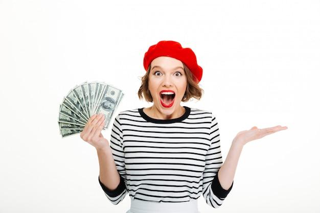 Gelukkige gillende dame die geïsoleerde gelddollars toont