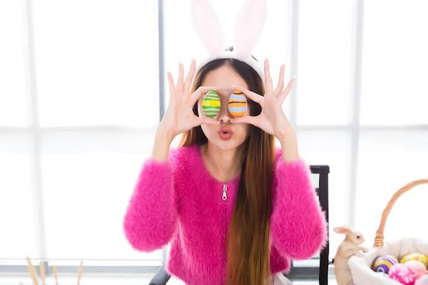 Gelukkige glimlach aziatische jonge vrouw die konijntjesoren draagt en een kleurrijk paasei steunt