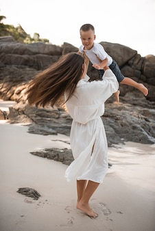 Gelukkige glimlach europese familie heeft rust en loopt op wit zandstrand.