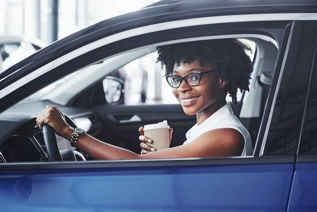 Gelukkige glimlach. jonge afro-amerikaanse vrouw zit binnenkant van nieuwe moderne auto.