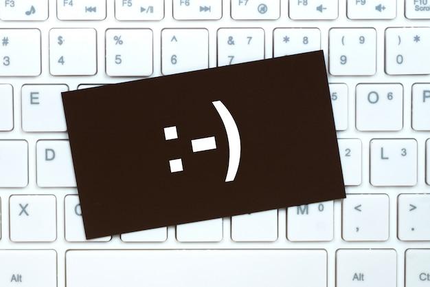 Gelukkige glimlach op een papieren kaart op een toetsenbord achtergrond