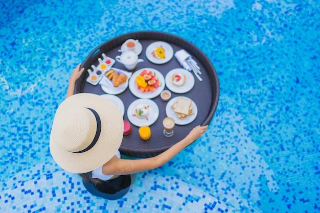 Gelukkige glimlach van de portret de mooie jonge aziatische vrouw met drijvend ontbijt in dienblad op zwembad