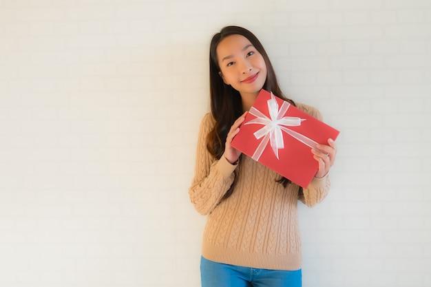 Gelukkige glimlach van de portret de mooie jonge aziatische vrouw met giftdoos
