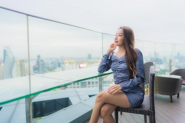 Gelukkige glimlach van de portret de mooie jonge aziatische vrouw op dak hoogste restaurant rond stadsmening