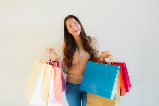 Gelukkige glimlach van de portret de mooie jonge aziatische vrouwen met het winkelen zak
