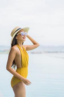 Gelukkige glimlach van de portret ontspant de aziatische mooie jonge vrouw rond openlucht zwembad in vakantievakantie