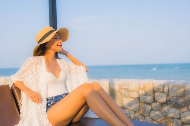 Gelukkige glimlach van de portret ontspant de jonge aziatische vrouw rond strand overzeese oceaan