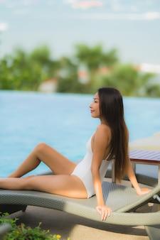 Gelukkige glimlach van de portret ontspant de jonge aziatische vrouw rond zwembad in hoteltoevlucht