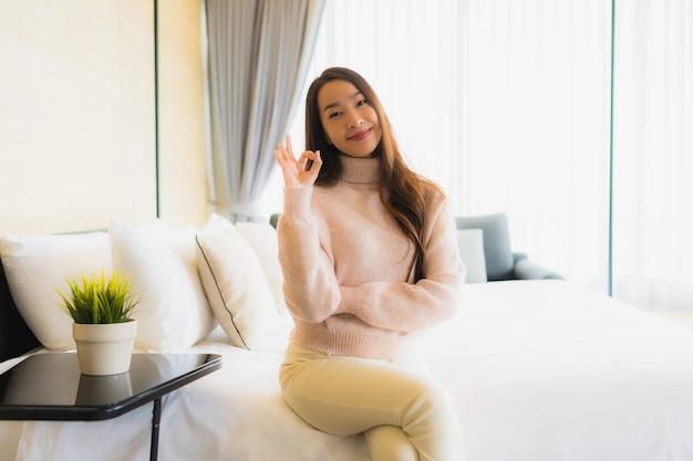 Gelukkige glimlach van de portret ontspant de mooie jonge aziatische vrouw op bed