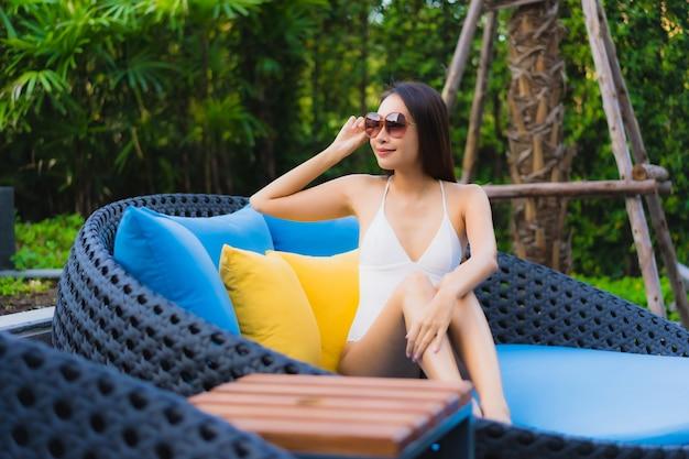 Gelukkige glimlach van de portret ontspant de mooie jonge aziatische vrouw rond openlucht zwembad