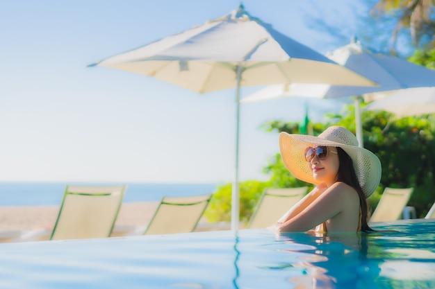 Gelukkige glimlach van de portret ontspant de mooie jonge aziatische vrouw rond openluchtzwembad in hoteltoevlucht