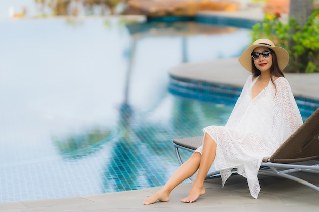 Gelukkige glimlach van de portret ontspant de mooie jonge aziatische vrouw rond zwembad in hoteltoevlucht
