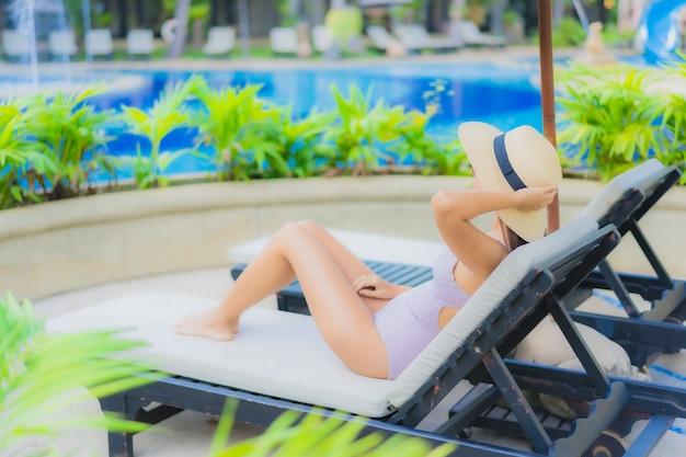 Gelukkige glimlach van de portret ontspant de mooie jonge aziatische vrouwen rond openlucht zwembad