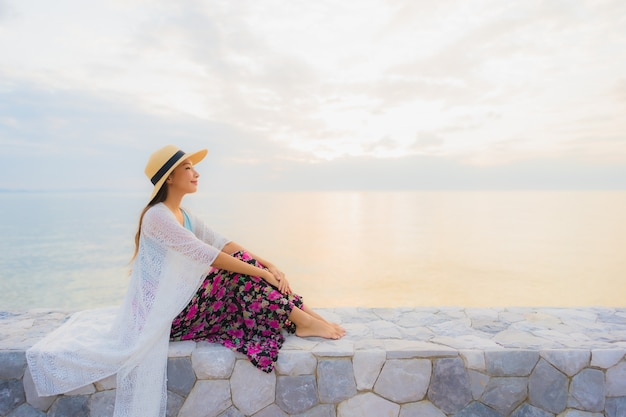 Gelukkige glimlach van de portret ontspant de mooie jonge aziatische vrouwen rond overzeese strandoceaan
