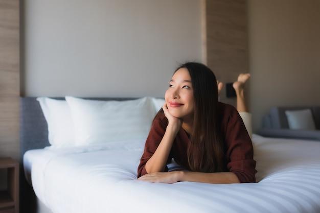 Gelukkige glimlach van portret ontspant de mooie jonge aziatische vrouwen op bed