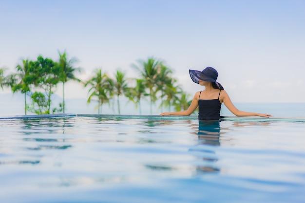 Gelukkige glimlach van portret ontspant de mooie jonge aziatische vrouwen openlucht zwembad in hotel