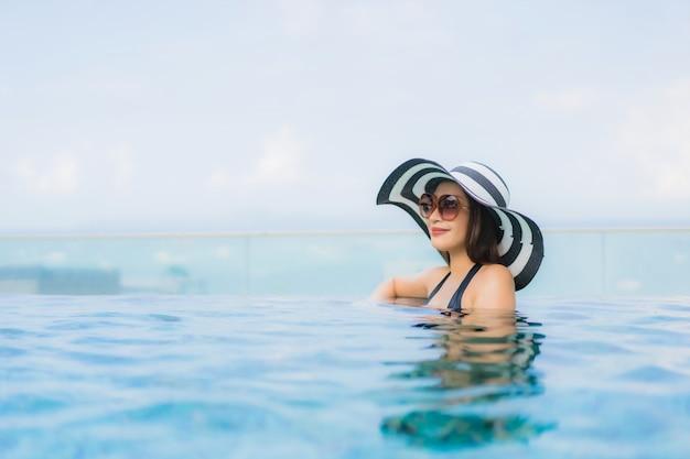 Gelukkige glimlach van portret ontspant de mooie jonge aziatische vrouwen openlucht zwembad in toevlucht