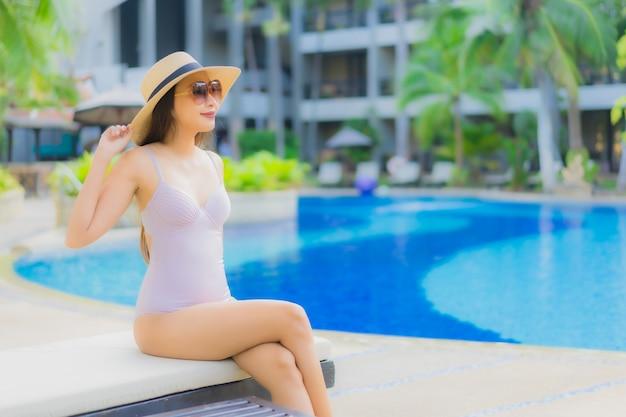 Gelukkige glimlach van portret ontspant de mooie jonge aziatische vrouwen rond openlucht zwembad