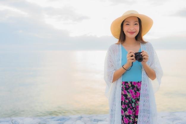 Gelukkige glimlach van portret ontspant de mooie jonge aziatische vrouwen rond overzeese strandoceaan