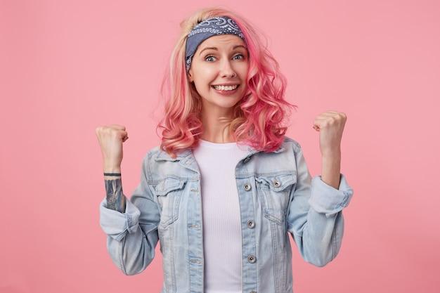 Gelukkige glimlachende aardige dame met roze haar en getatoeëerde handen, staand, gekleed in een wit t-shirt en spijkerjasje. kijkt, viert overwinning met vuisten.