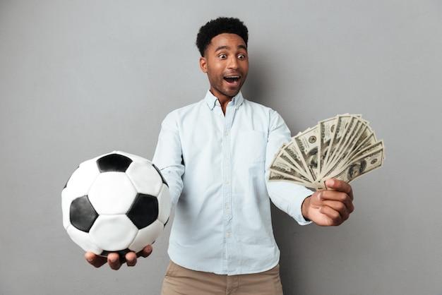 Gelukkige glimlachende afrikaanse mens die voetbal en geldbankbiljetten toont