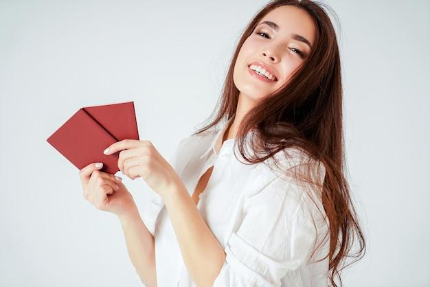 Gelukkige glimlachende aziatische jonge lange haarvrouw met twee paspoorten op witte geïsoleerde achtergrond