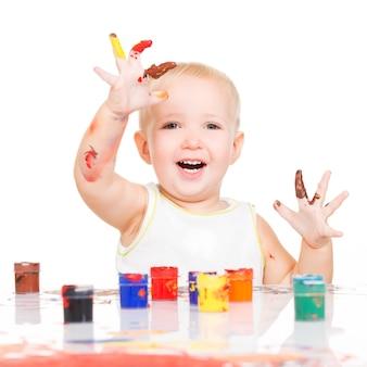 Gelukkige glimlachende baby met geschilderde die handen op wit wordt geïsoleerd.