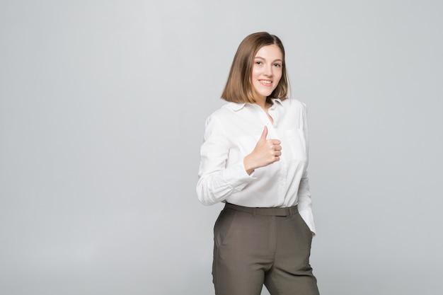 Gelukkige glimlachende bedrijfsvrouw met duimen omhoog gebaar, dat op witte muur wordt geïsoleerd
