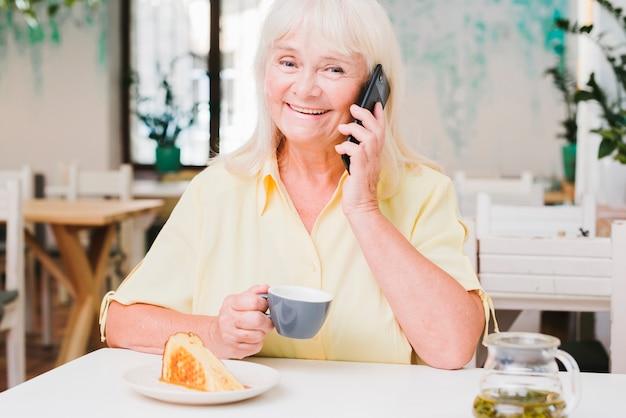 Gelukkige glimlachende bejaarde die op telefoon spreekt