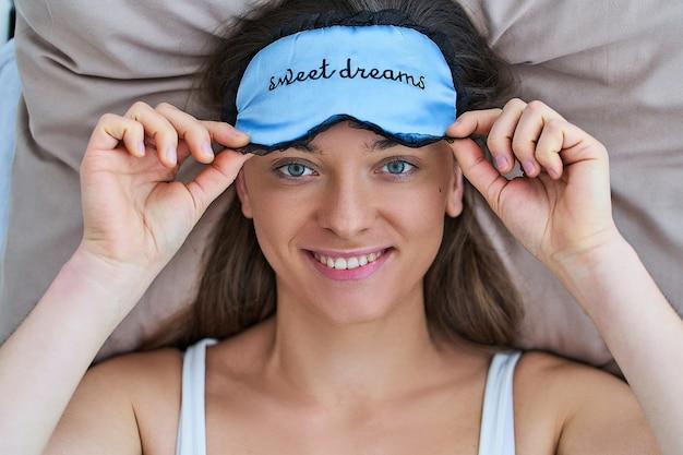 Gelukkige glimlachende blije vrouw die oogmasker gebruikt voor beter slapen en zoete dromen