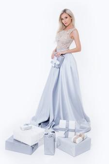 Gelukkige glimlachende blondevrouw in lange zilveren kleding met giftdoos bij de witte geïsoleerde achtergrond