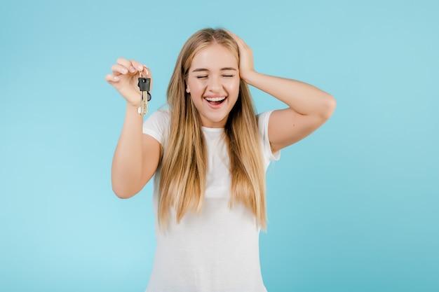 Gelukkige glimlachende blondevrouw met sleutels van flat die over blauw wordt geïsoleerd