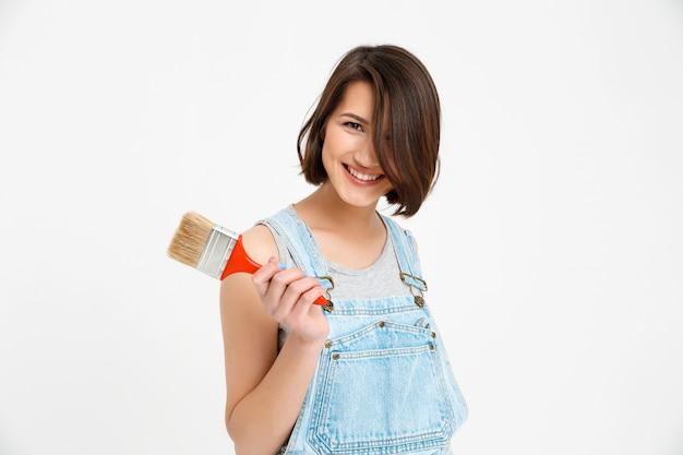 Gelukkige, glimlachende creatieve vrouw met het schilderen van borstel