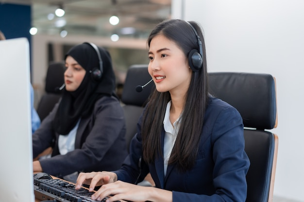 Gelukkige glimlachende de dienstagent van de exploitant aziatische vrouw met hoofdtelefoons die aan computer in een call centre werken