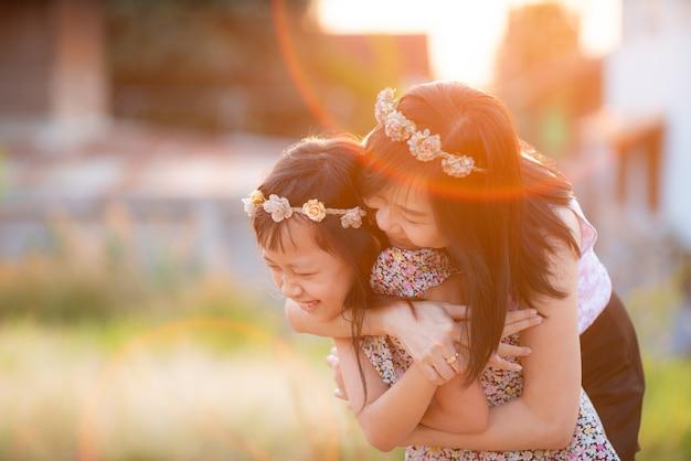 Gelukkige glimlachende dochter en haar moeder die in openlucht koesteren