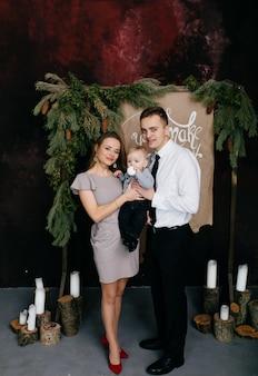 Gelukkige glimlachende familie bij studio op achtergrond van de kerstboom met gift